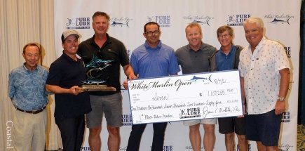 group of men holding big check for winning first place in the blue marlin category