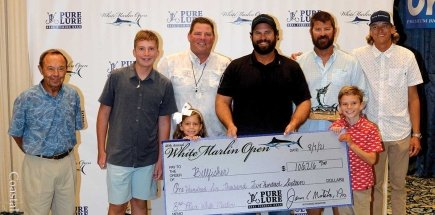 group of men holding check for third place white marlin open